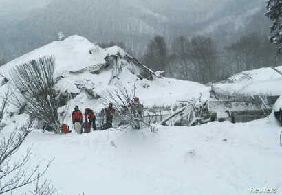 Members of Lazio's Alpine and Speleological Rescue Team stand in front of the Hotel Rigopiano in Farindola, Italy, that was hit by an avalanche, Jan. 19, 2017.