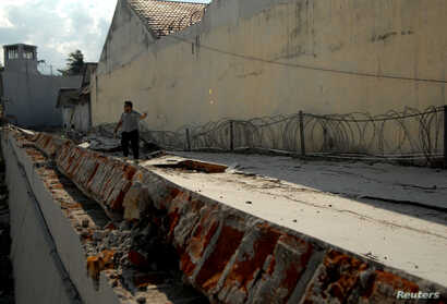 An officer walks at a collapsed prison following an earthquake in Palu, Central Sulawesi, Indonesia, Oct. 2, 2018.