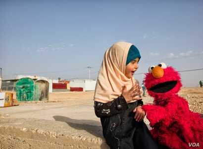 Elmo visits a young girl in a refugee camp. Sesame Workshop, together with the International Rescue Committee, have teamed up in an effort to provide quality education to young children displaced by conflict and persecution. (Photo: courtesy Sesame W...