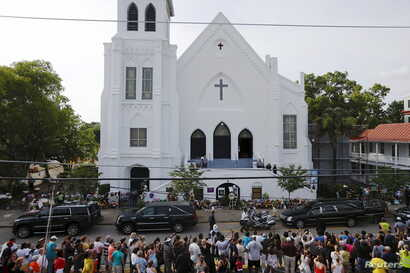 Members of the public line along the street as a hearse carrying the Reverend Clementa Pinckney arrives at the Emanuel African Methodist Episcopal Church for a public viewing in Charleston, South Carolina, June 25, 2015.