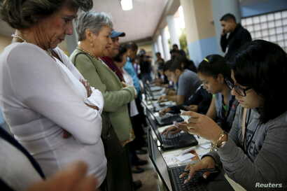 People register to cast their vote at a polling station during a legislative election, in Caracas, Venezuela, Dec. 6, 2015.
