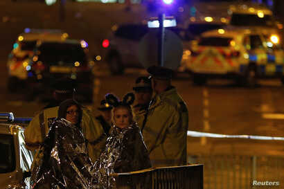 Two women wrapped in thermal blankets look on near the Manchester Arena, where U.S. singer Ariana Grande had been performing, in Manchester, northern England, Britain, May 23, 2017