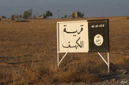 "While coalition airstrikes rain down on IS in Mosul, soldiers say the Iraqi Army's southern front is largely a ground operation pushing slowly towards the city.  This old IS road sign at least 50 kilometers from Mosul still stands, saying ""The Villag..."