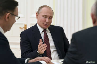 Russian President Vladimir Putin meets with co-chairs of his campaign office at the Kremlin in Moscow, March 19, 2018.
