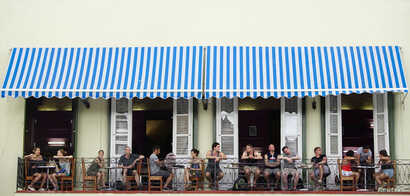 Tourists sit in a balcony at a restaurant in Old Havana, Cuba, April 28, 2017.