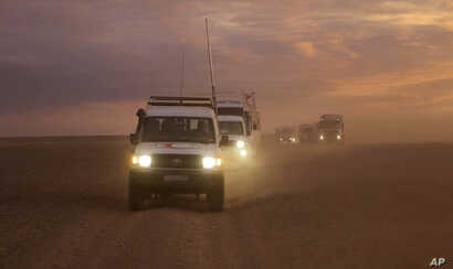 This photo released by the Syrian Arab Red Crescent, shows a convoy of vehicles of the Syrian Arab Red Crescent driving in the Syrian desert heading to Rukban camp between the Jordan and Syria borders, Nov. 4, 2018.
