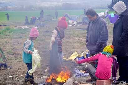 Refugees at Idomeni camp keep warm by burning a soiled blanket. (Jamie Dettmer for VOA)