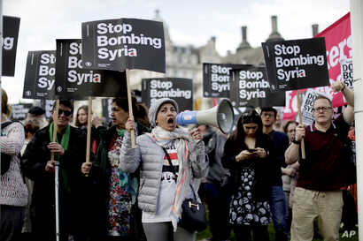 Demonstrators take part in a protest organized by the Stop the War coalition against the British government carrying out airstrikes on targets in Syria, in Parliament Square, London, April 16, 2018.