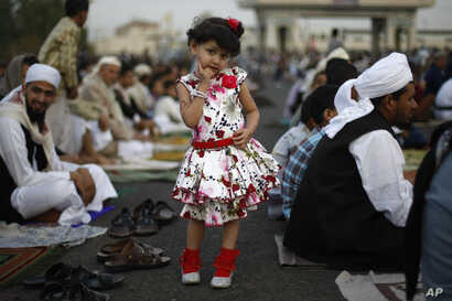 A Yemeni girl poses for a photograph as she attends the Eid al-Fitr prayer with her father, in Sanaa, Yemen, Monday, July 28, 2014. Monday marked the beginning of the three-day Eid al-Fitr holiday, which caps the Muslim fasting month of Ramadan. Musl...