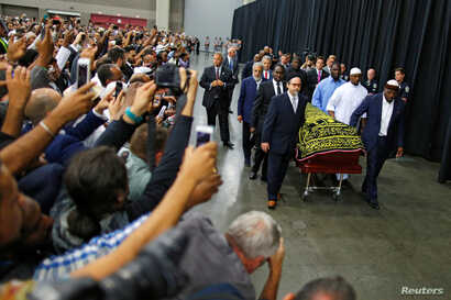 Worshippers and well-wishers take photographs as the casket with the body of the late-boxing champion Muhammad Ali is brought for his Jenazah, an Islamic funeral prayer, in Louisville, Ky., June 9, 2016.