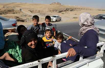 People return back to Kirkuk, 290 kilometers (180 miles) north of Baghdad, Oct. 17, 2017. Thousands of civilians are streaming back to Kirkuk, a day after fleeing as Iraqi troops pushed Kurdish forces out of the disputed oil-rich city.