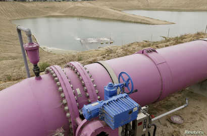 A purple pipe feeds recycled wastewater to a holding pond to recharge an underground aquifer at the Orange County Water District recharge facility in Anaheim, Calif, May 8, 2015.