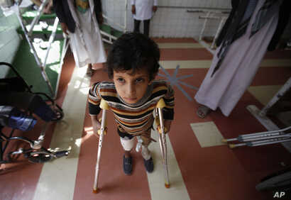 FILE - A young boy who lost his leg in the Yemen war uses a prosthetic limb at a government-run rehabilitation center in Sanaa, Yemen, Saturday, March 5, 2016.