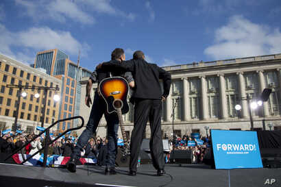 President Barack Obama stands with singer Bruce Springsteen as he arrives to speak at a campaign event in Madison, Wisconsin, Nov. 5, 2012.