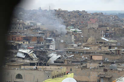 Mosul's Old City, seen through a sniper hole on the outskirts, is the scene of some of the fiercest fighting since operations to retake the city from IS militants began in October.  Mosul, March 25, 2017.