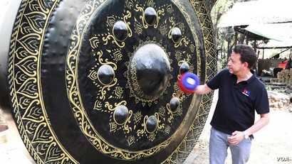 VOA correspondent Steve Herman tries his hand at ringing a giant gong. (Z. Aung/VOA)