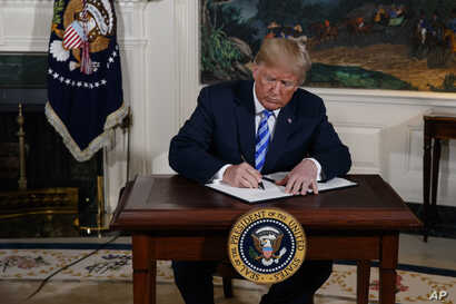President Donald Trump signs a Presidential Memorandum on the Iran nuclear deal from the Diplomatic Reception Room of the White House, May 8, 2018.