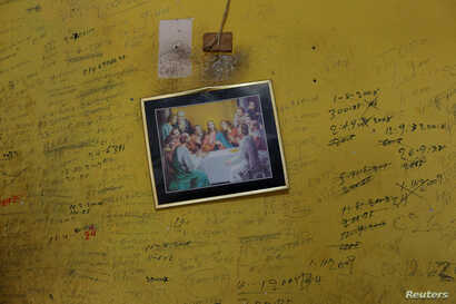 """Annotations with the record of the incomes and expenses of the house, are written on the wall next to an illustration depicting """"The Last Supper"""" in the house of Juan Pulgar, his daughter Zulay and their family in Punto Fijo, Venezuela Nov. 17, 2016...."""