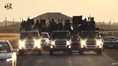 FILE - An image grab taken from a video released by Islamic State group's official Al-Raqqa site via YouTube allegedly shows Islamic State (IS) group recruits riding in armed trucks in an unknown location.