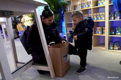 A federal worker left unpaid or furloughed collects a free bag of groceries with a child from Kraft Foods on the 27th day of the partial government shutdown in Washington, U.S., Jan. 17, 2019