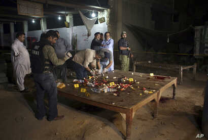 Pakistani investigators collect evidence from the site of a shooting in Karachi, Pakistan, June 23, 2017. Gunmen in the port city of Karachi attacked police officers at a roadside restaurant and killed four of them before fleeing, according to senior...