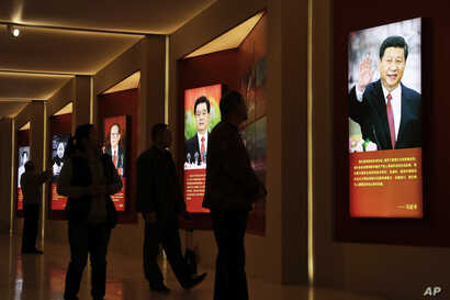 Visitors walk past images of China's past and present leaders, from left, Mao Zedong, Deng Xiaoping, Jiang Zemin, Hu Jintao and Xi Jinping on display at an exhibition on the Long March at the military museum in Beijing, Oct. 24, 2016.