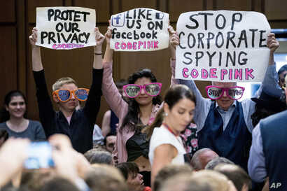 "Members of the audience hold up signs and wear sunglasses that read ""Stop Spying"" before CEO Mark Zuckerberg arrives to testify before a joint hearing of two Senate committees on Capitol Hill in Washington, April 10, 2018, about the use of Facebook d..."
