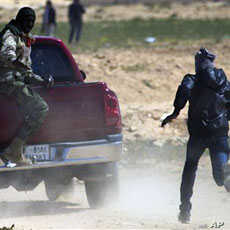 Libyan rebels run to take cover as mortars from Moammar Gadhafi's forces are fired on them on the frontline near Zwitina, the outskirts of the city of Ajdabiya, south of Benghazi, eastern Libya, Mar 23 2011