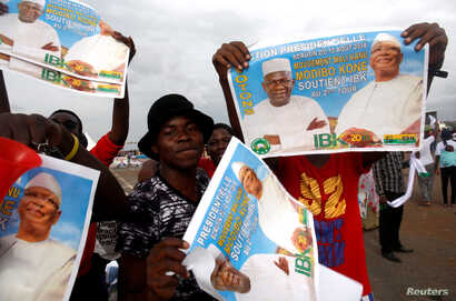 Supporters of Ibrahim Boubacar Keita, president of Mali and candidate for Rally for Mali party, carry his pictures during a rally in Bamako, ahead of the second round of the country's presidential election, in Mali, Aug. 10, 2018.