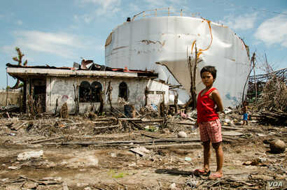 A girl wanders near a typhoon-damaged house and oil tank in the Filipino town of Tanauan in 2013. The Millennium Challenge Corp. supported rehabilitation efforts with the Peace Corps response program.