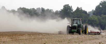 FILE - In this May 31, 2007, file photo, a farm tractor stirs up dust as it moves across a field on a farm along state road 82 near Tifton, Georgia.