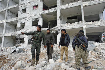 Fighters of the Kurdish People's Protection Units (YPG) stand on the debris of a damaged building in the northern Syrian town of Kobani January 28, 2015.