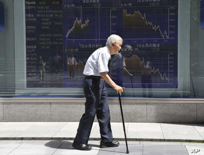 FILE - An elderly man walks by an electronic stock board of a securities firm in Tokyo, Aug. 19, 2016.