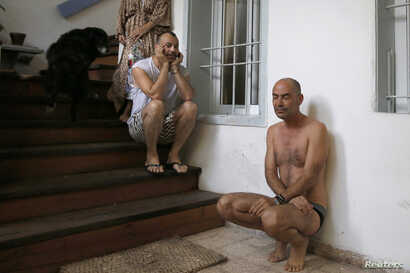 Israelis take cover in a stairwell as an air raid siren, warning of incoming rockets, sounds in Tel Aviv July 9, 2014.