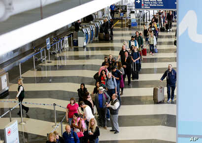 A long line of travelers wait for the TSA security check point at O'Hare International airport, Monday, May 16, 2016, in Chicago.
