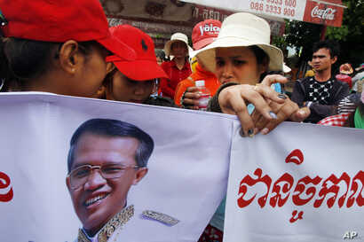 FILE - Cambodia garment workers hold banners  with a portrait of Prime Minister Hun Sen while authority prevent them from reaching the prime minister's residence in Phnom Penh, Cambodia.