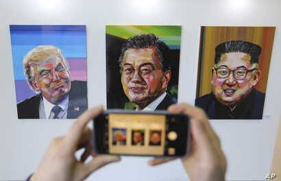 A visitor takes images, from left, of U.S. President Donald Trump, South Korean President Moon Jae-in and North Korean leader Kim Jong Un during an exhibition at an annex of the presidential Blue House in Seoul, South Korea, Jan. 3, 2019.
