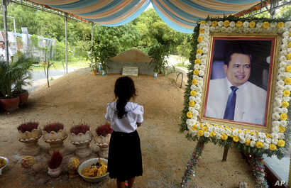 FILE - A girl stands by a portrait of Kem Ley, a Cambodian prominent political analyst, at his grave in Ang Takok, Cambodia, Nov. 20, 2016.