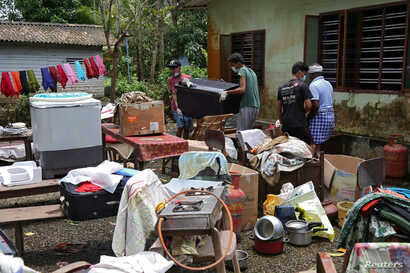 Volunteers collect household items in the lawns of a residential house before cleaning the house following floods in Kuttanad in Alappuzha district in the southern state of Kerala, India, Aug. 28, 2018.