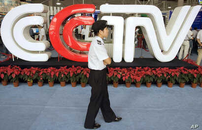 FILE - A security guard walks past the logo for China Central Television (now China Global Television Network)  in Beijing Thursday, Aug. 24, 2006.