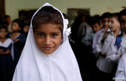 A girl attends morning assembly at the Mashal Model school in Islamabad, Pakistan, Sept. 29, 2017.