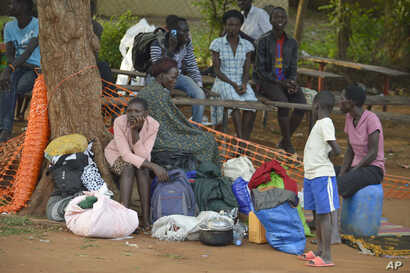 In this Tuesday July 12, 2016 photo, people take shelter near the All Saints Church in Juba, South Sudan. Embassies and aid organizations in South Sudan were trying to evacuate staff from the capital, Juba, on Tuesday as a precarious calm settled ove