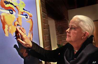 FILE: Former rock singer Grace Slick touches her painting of the late rock star Jimi Hendrix Nov. 16, 2000, at the Artrock gallery in San Francisco. (AP Photo/Ben Margot).
