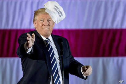 FILE - President-elect Donald Trump throws a hat into the audience while speaking at a rally in a DOW Chemical Hanger at Baton Rouge Metropolitan Airport, Dec. 9, 2016