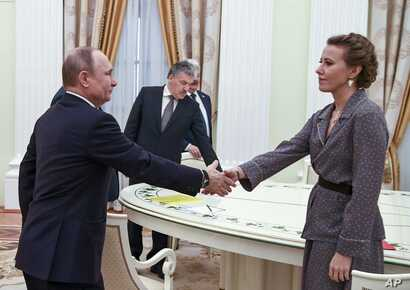 Russian President Vladimir Putin, left, greets Ksenia Sobchak, right, during his meeting with opposition candidates who ran against him in Sunday's presidential election, Boris Titov, Sergei Baburin, Maxim Suraykin, Vladimir Zhirinivsky, Pavel Grudin...