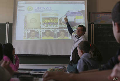 FILE - Ari Mascarenhas teaches students Portuguese using the World Cup sticker book, in Sao Paulo, Brazil, May 21, 2018.