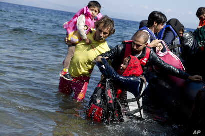 Afghan migrants arrive on the shores of the Greek island of Lesbos after crossing the Aegean sea from Turkey on a inflatable dinghy, Sept. 25, 2015.
