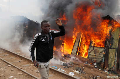 A supporter of opposition leader Raila Odinga runs past a burned shack, in Kibera slum, Nairobi, Kenya, Aug. 12, 2017.
