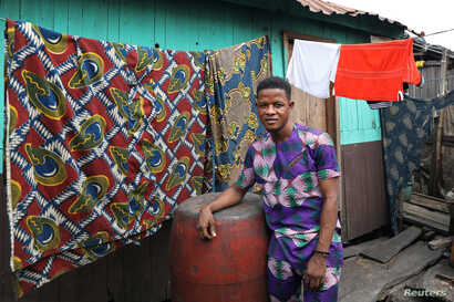 John Sunday, 23-year-old student and first-time voter, poses for a picture in the Makoko shanty town built on stilts in a lagoon in Lagos,  Feb. 4 , 2019.