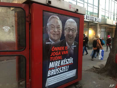 """A phone box displays a billboards showing Hungarian-American financier George Soros and EU Commission President Jean-Claude Juncker above the caption """"You have a right to know what Brussels is preparing to do!,"""" on Vaci Avenue in Budapest, Hungary,..."""